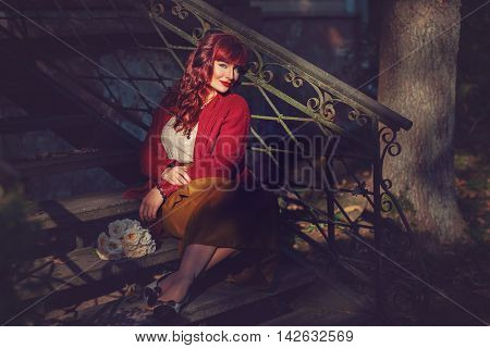 Beautiful young woman in long skirt and wool red scarf sitting on old house stairs. Early fall. Outside shot. Ambient light. Copy space.