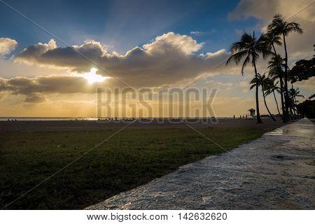 Honolulu, Hawaii, USA - Dec 21, 2015: Setting sun over beach at Ala Moana Park, along Ala Moana Park Drive. The beach overlooks Mamala Bay.