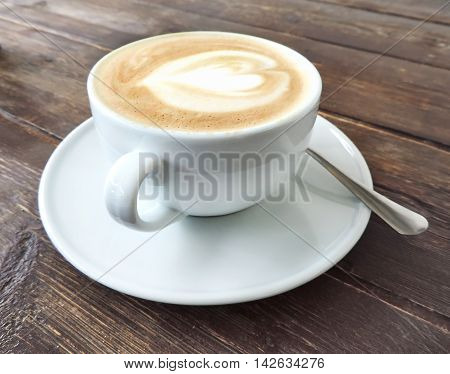 Cup of coffee or cappuccino on a wooden table.