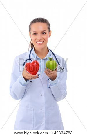 Beautiful smiling female doctor holding red heart and green apple