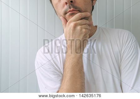 Man with hand on chin thinking deep thoughts and making tough decisions