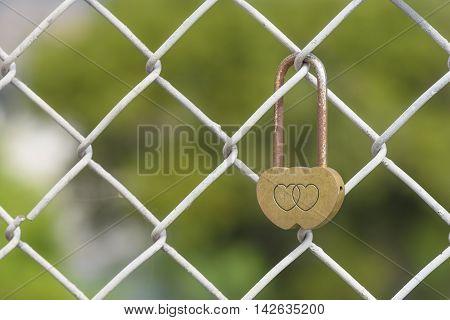 Closeup rusty heart shaped padlock locked on iron chain