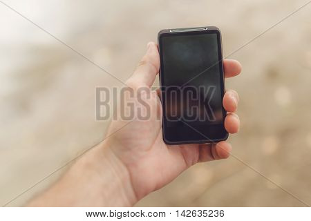 Male hand with mobile phone on the beach selective focus