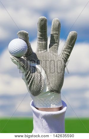 glove with golf ball, backdrop of the beautiful blue sky