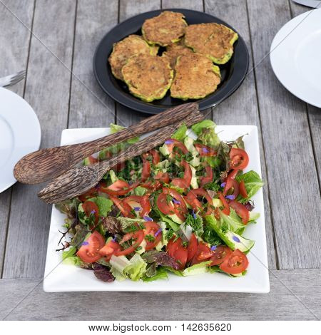 Salad of lettuce tomatoes and edible flowers with zucchini or courgette fritters served outdoors on a wooden table.