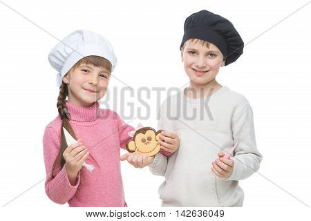 Beautiful boy and girl in chef hats holding monkey shape christmas cookie. Children standing isolated over white background.