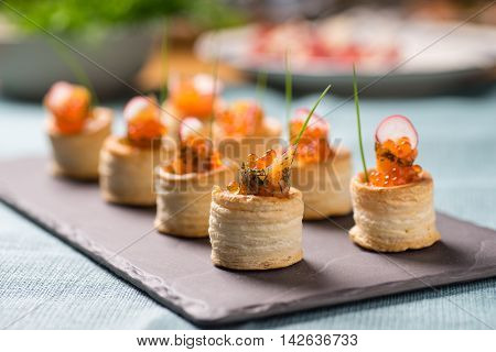 Delicious appetizers with graved salmon and golden caviar served in puff pastry towers