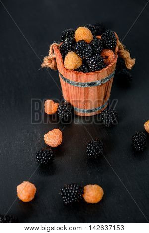 Black Amd Yellow Raspberries In A Wooden Basket And On   Table. Close Up.