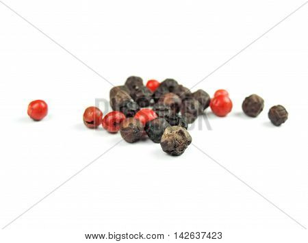 Red and black peppercorns, isolated on white background.