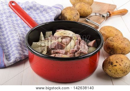 cooked onions and bacon cubes with coarse pepper in a pot next to raw potatoes and vegetable peelers