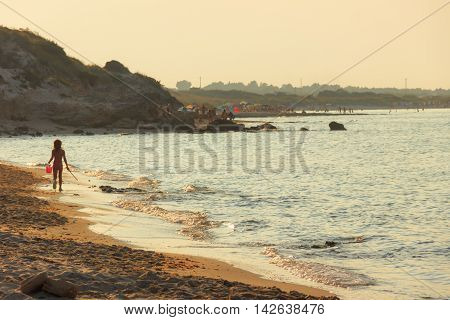 Apulia seascape: Nature Reserve of Torre Guaceto, Brindisi, Italy. Walk on the shore into the sunset.Child walks at sunset on the shore.