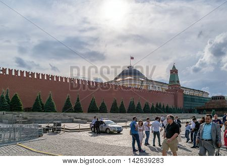 Moscow, Russia - July 07, 2016: Police officers with a car on duty near the Kremlin wall on Red Square on which people walk