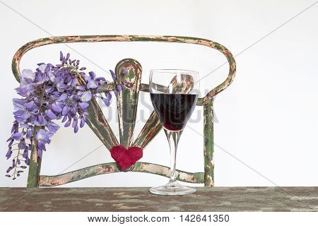 glass of red wine over the wooden table, background old iron chair with wisteria flowers and a heart, white background