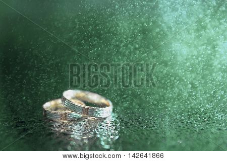 Wedding rings with rain drops closeup. Soft Focus.