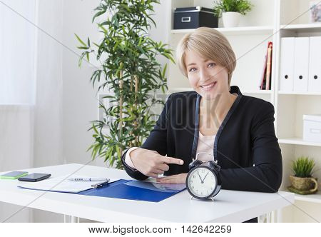 beautiful business woman in the office at the table shows the clock and smiling
