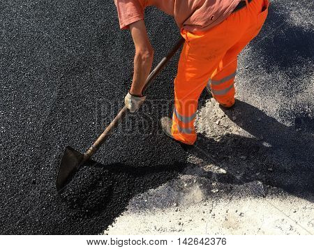 manual asphalting of a road in summer