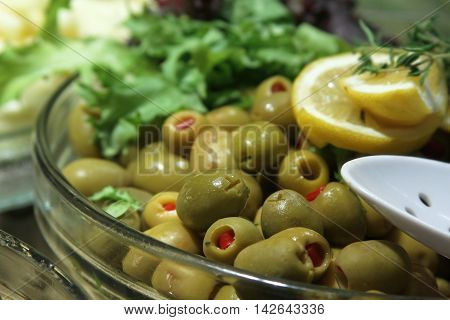 Green olives with lemon and greens on the plate