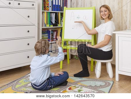 young beautiful woman teacher involved with a pupil at the blackboard. Pupil sitting on the floor raised his hand to answer. horizontal color image.