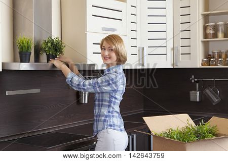 beautiful young blond woman has moved into a new house and decorate your kitchen. Smiling and looking into the camera