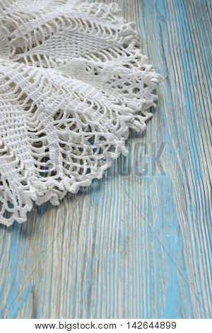 Handmade crocheted cotton organic doily on wooden background. Old crocheting hook