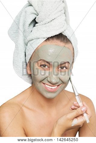Young woman applying facial clay mask to her face using brush