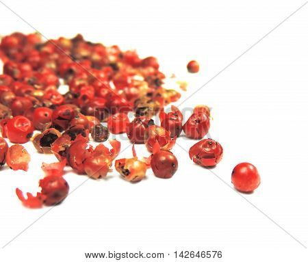 Red peppercorns with selective focus, isolated on white background.