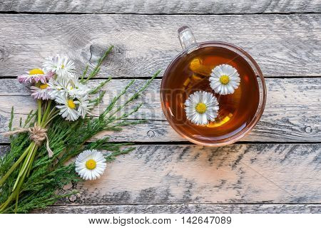 Healthy herbal tea. Chamomile and juniper  drink and wildflowers bouquet on vintage wooden table. Top view