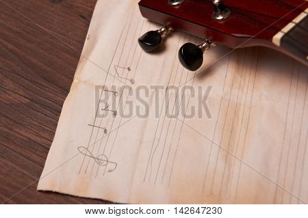Ukulele and musical old paper notes on wooden table