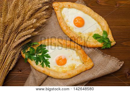 Appetizing open pies with cheese and eggs on sackcloth