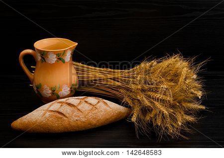 Sheaf a clay jug and rye bread on a black background