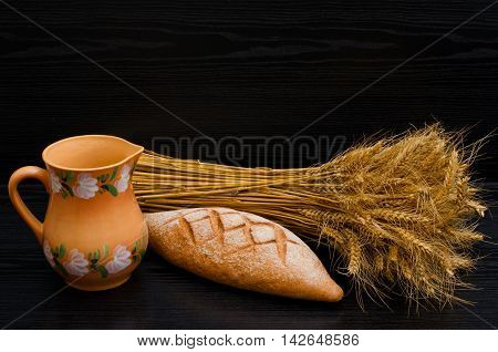 Clay pitcher rye bread and a sheaf on a black background