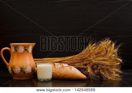 Clay jug a glass of milk rye bread and a sheaf on a black background