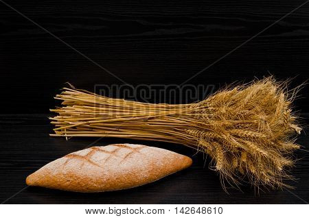 Delicious rye bread and a sheaf on a black background