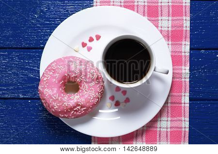 Pink donut with cup of hot coffee on a blue wooden table top view