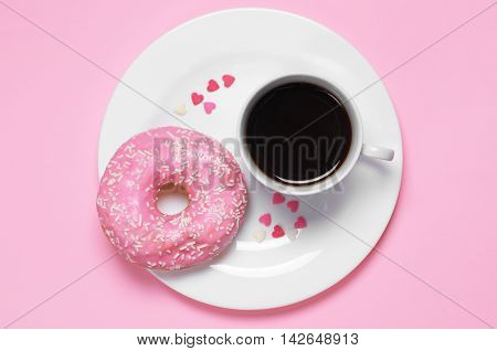 Plate with cup of hot coffee and sweet donut. Photo in a pink color scheme top view