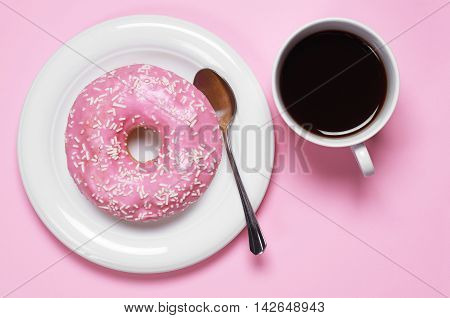 Donut with cup of hot coffee top view. Photo in a pink color scheme