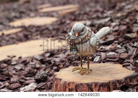 Figurines - Bird on a stub on a wooden stub background