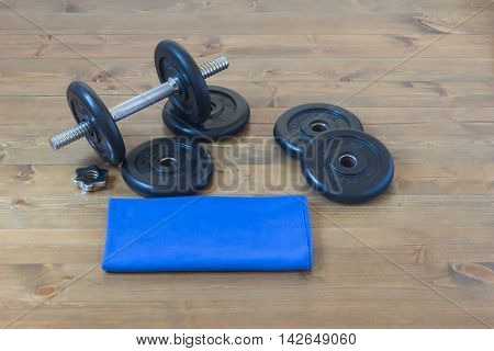 dumbbells with a blue towel sports, on a wooden background floor