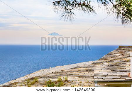 Roof of the old monastery house, seascape and mount Athos far away in the clouds, Greece