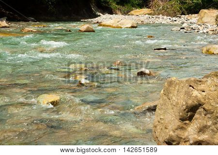 Cold fast running river more beautiful stones