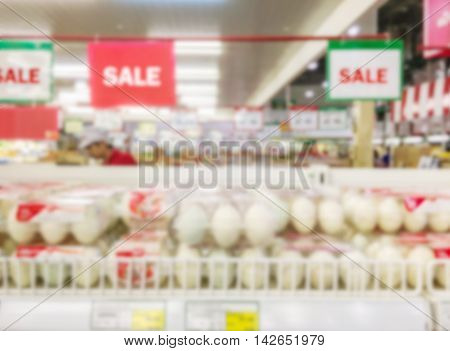 Motion blur of duck egg shelves for sale in supermarket with some people shopping