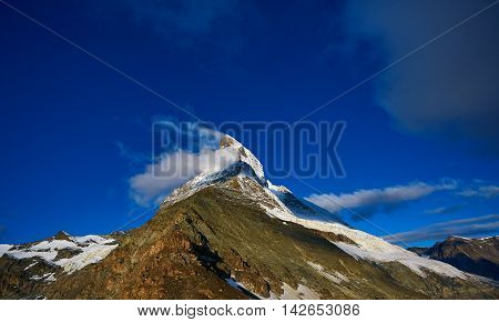 Snow capped mountains. Matterhorn mount in the clouds at early morning. view of the north- eastern ridge . Trek near Matterhorn mount.