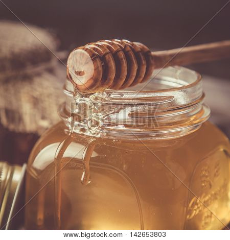 Golden honey in glass jar with dipper, dark photo