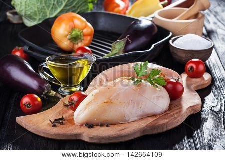 raw chicken fillets on wooden cutting board, with vegetables and pan grill
