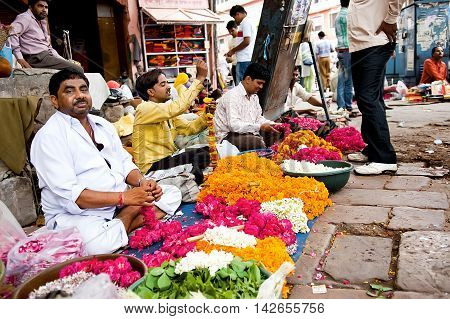 Jaipur India - Jule 29 2011: Men threading colourful flower garlands. These flowers are offered to the gods in the temples