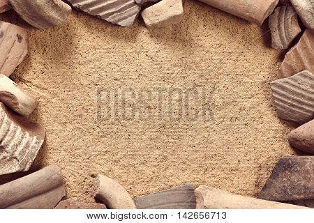 Frame of ceramic shards of antique crockery on sandstone background. Archaeological concept