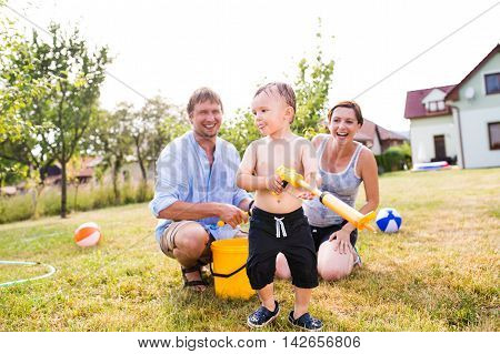 Boy With Mother And Father After Splashing Each Other