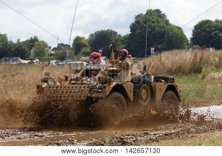 WESTERNHANGER, UK - JULY 25: An ex British Army Ferret scout car makes the most of the muddy conditions in the display arena at the War & Peace show on July 25, 2015 in Westernhanger