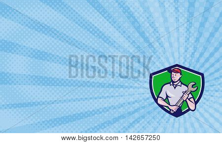 Business card showing illustration of a mechanic worker standing looking to the side carrying spanner viewed from front set inside shield crest on isolated background done in cartoon style.