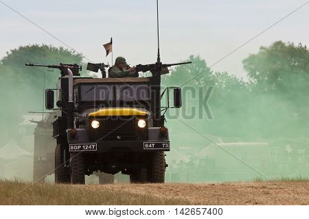WESTERNHANGER, UK - JULY 23: An ex US army gun lorry enters the main arena with all guns blazing as part of a Vietnam war re-enaction at the W&P show on July 23, 2015 in Westernhanger